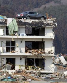<p>KAOS: En bil har havnet på taket i byen Minamisanriku etter at tsunamien raserte området.</p>