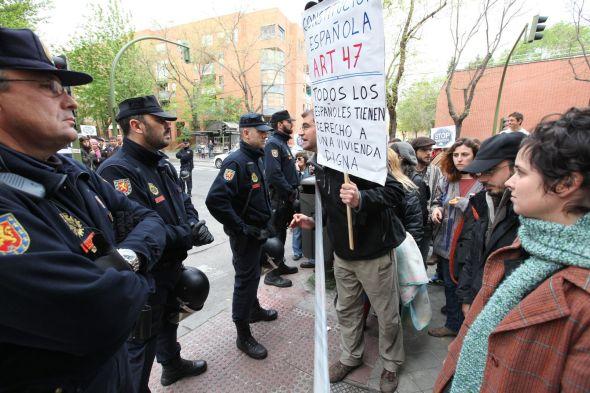 FRONTLINJE: Demonstranter protesterer mot utkastelsen av Maria Luisa Pintales i Madrid og roper slagord mot politiet. Politisjefen på stedet leser på en plakat, hvor det står skrevet: «Den spanske konstitusjonen artikkel 47. Alle spanjoler har rett til å ha et anstendig husrom».