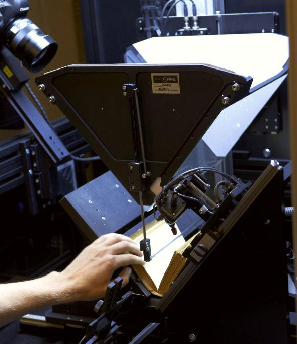 <p><b>Blar og skanner:</b> Til å skanne gjennom alle bøkene brukes det egne maskiner som blar og avfotograferer bøkene.</p>