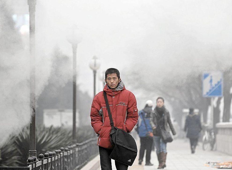 I RØYKEN: En kineser spaserer forbi et anlegg i Peking.
